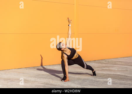 Young beautiful yogi woman practicing yoga, doing utthita trikonasana exercise, extended triangle pose, working out, wearing sportswear black pants an - Stock Image