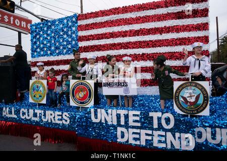Children dressed in military uniforms ride on float recognizing branches of the U.S. military during parade in downtown Laredo, Texas. - Stock Image