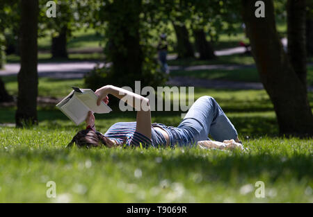 People enjoy the sunshine in Glasgow's Kelvingrove Park as the hot weather continues. - Stock Image