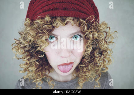 Close-up portrait of a beautiful and funny young woman with blue eyes and curly blonde hair sticking out her tongue wearing a red woolen cap - Stock Image