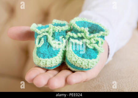 Crop hand with tiny green footwear on it - Stock Image