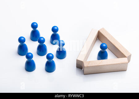 Close-up Of Figurine Pawn Separated By Wooden Blocks From Blue Figurines Over White Background - Stock Image