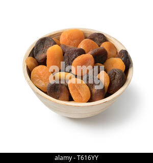 Bowl with orange and brown dried apricots isolated on white background - Stock Image