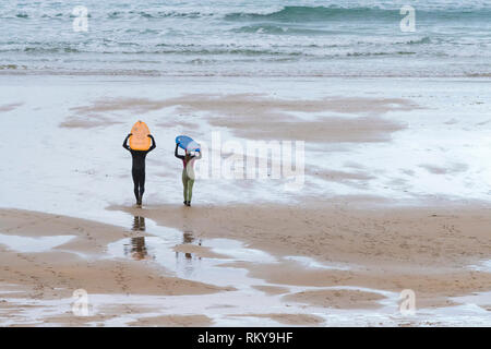 Two surfers carrying their surfboards on their heads and walking down to the sea on Fistral Beach in Newquay in Cornwall. - Stock Image