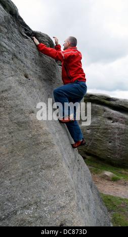 rock climber Doug Blane bouldering at Burbage Edge South, Derbyshire, Peak District National Park, England, UK, - Stock Image