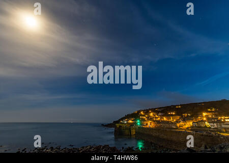 Mousehole, Cornwall, UK. 16th April 2019. UK Weather. After a day of sunshine, clear skies in the evening revealing the nearly full moon over the harbour town of Mousehole. Credit: Simon Maycock/Alamy Live News - Stock Image