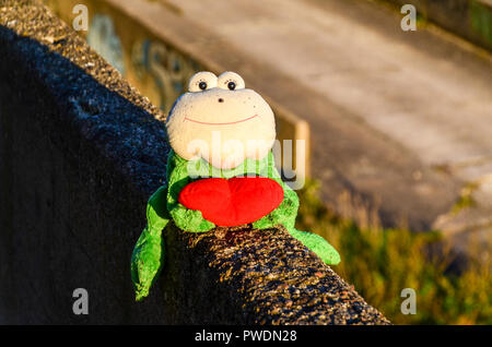 Frog puppet with a read heart, abandoned in Vilnius, Lithuania, at sunset - Stock Image