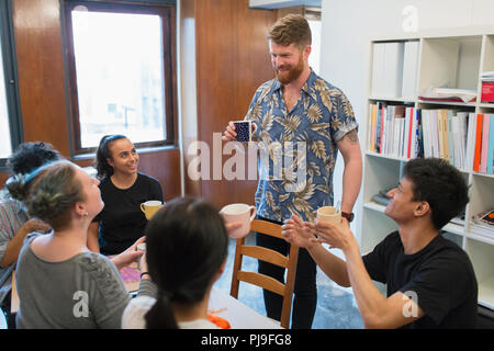 Creative business people enjoying coffee and tea in office - Stock Image