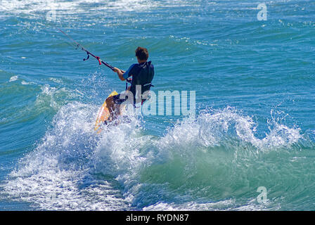 Kite boarder jumping a wave during a windy day in french riviera - Stock Image