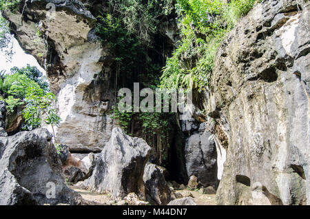 stone cliff with a dark cave mouth - Stock Image