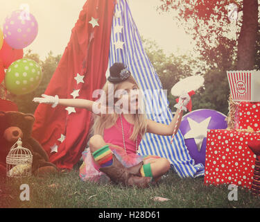 A little child is pretending to perform at a circus theme background with party balloons for an imagination, art - Stock Image