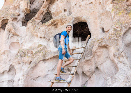 Man tourist happy climbing ladder on Main Loop trail path in Bandelier National Monument in New Mexico during summer by canyon cliff - Stock Image