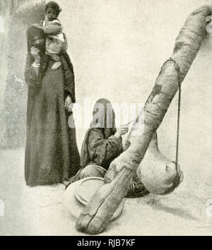 Arab woman with a goatskin butter churn suspended from the broken stem of a date palm, at a village near Cairo, Egypt. A woman stands alongside with a child sitting on her shoulder. - Stock Image