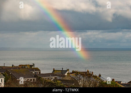 Mousehole, Cornwall, UK. 4th Apr, 2019. UK Weather. A rainbow striking the sea at Mounts Bay, over a tiny fishing boat heading back to Newlyn after a day out fishing. Credit: Simon Maycock/Alamy Live News - Stock Image