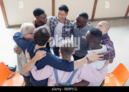 Men hugging in circle in group therapy - Stock Image