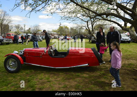 Floral Park, New York, U.S. 27th April, 2014. A family with young children looks at a red BRA CX3, a custom Beribo Replica Automobiles kit vehicle with three wheels, and registered by DMV as a 2009 Custom Motorcycle, is exhibited at the 35th Annual Antique Auto Show at Queens Farm. Credit:  Ann E Parry/Alamy Live News - Stock Image