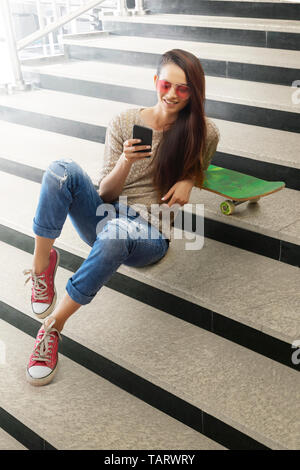 Woman sitting on steps with skateboard looking at mobile phone - Stock Image