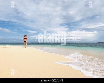 A women walks alone on a beach. Tavarua island resort, Fiji. - Stock Image