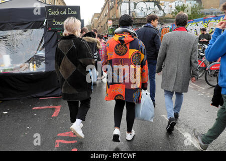Back view of couple walking along the street in winter man wearing beautiful yellow & orange coat Brick Lane East End East London E1 UK  KATHY DEWITT - Stock Image