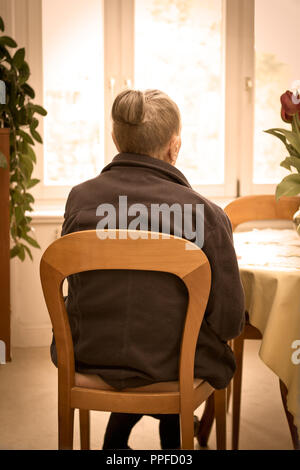 Old woman sitting at a table looking out of the window and thinking of the past, vintage filter effect, concept of nostalgia, fond memories. - Stock Image