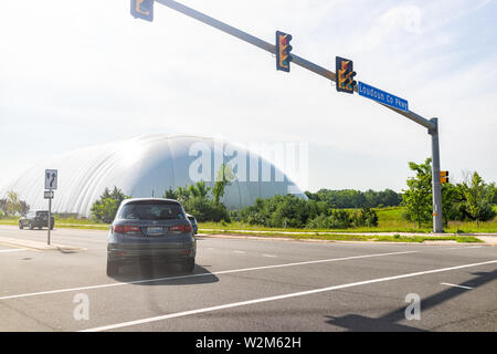 Ashburn, USA - May 29, 2019: Street highway road in Loudoun County, Virginia with parkway sign and road signal and cars turning in traffic by water ut - Stock Image