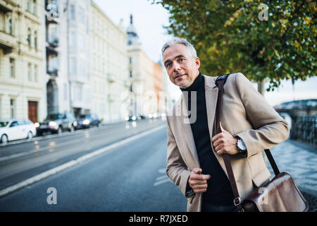 Mature businessman with bag standing on the street in city of Prague, waiting for a taxi cab. Copy space. - Stock Image
