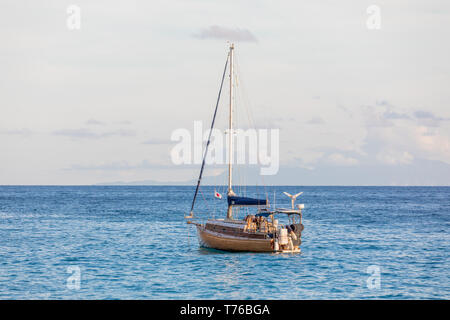 small sail boat at anchor off shell beach in St Barts - Stock Image