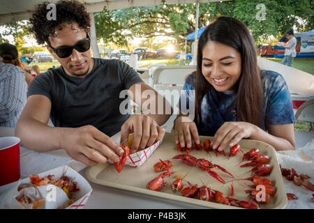 College age Hispanic couple picnic outdoors on seafood and have fun goofing off, Miami, Florida - Stock Image