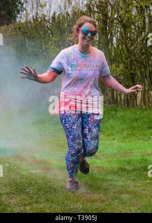 Female runner laughing and being covered in paint on Macmillan cancer charity 5K colour fun run. - Stock Image