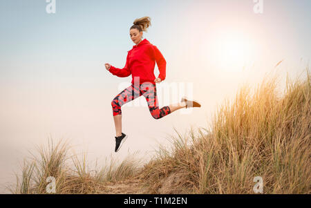 woman running through sand dunes - Stock Image
