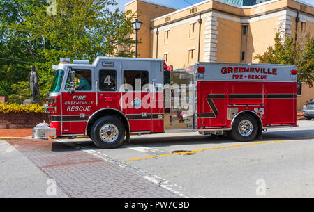 Greeneville, TN, USA-10-2-18: A red fire truck #4 stopped at an intersection, with the statue of President Andrew Johnson visible on the left. - Stock Image