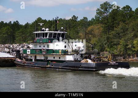 Tugboat pushes a barge westward on the Intracoastal Waterway through Orange Beach, Alabama. - Stock Image