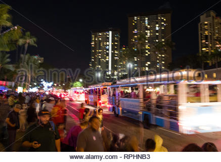 Motorized trolleys filled with people sightseeing the Honolulu City Lights Christmas celebration, Honolulu, Oahu, Hawaii, USA - Stock Image