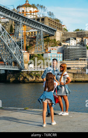 Porto, Portugal. April 29, 2019: Young girl takesk a picture of couple at the Ribeira in the Douro River bank near the Dom Luis I Bridge, Porto - Stock Image