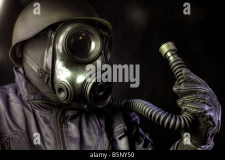 Gas masked man looking at his breathing tube - Stock Image