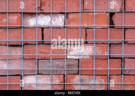 red brick wall behind wire metal fence, abstract background and symmetry, extra security measure - Stock Image