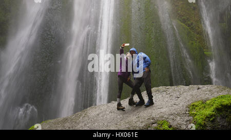 Low angle view of couple taking smartphone selfie standing on mossy boulder near waterfall in remote landscape - Stock Image