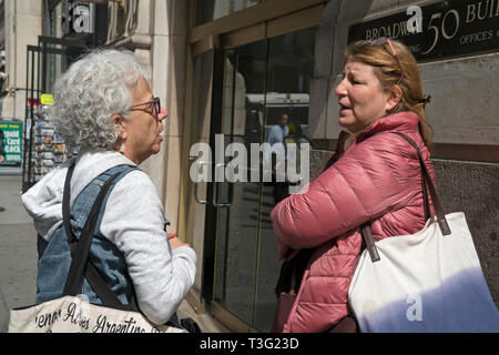 Two women having an earnest conversation on a sunny, spring day on Broadway in Lower Manhattan, New York City. - Stock Image