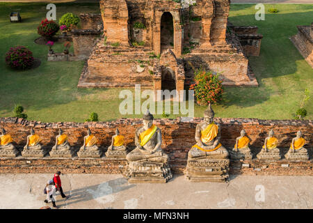 Two visitors walk past a row of Buddha statues at Wat Yai Chai Mongkhon, a 14th century Buddhist temple, Ayutthaya, Thailand. - Stock Image