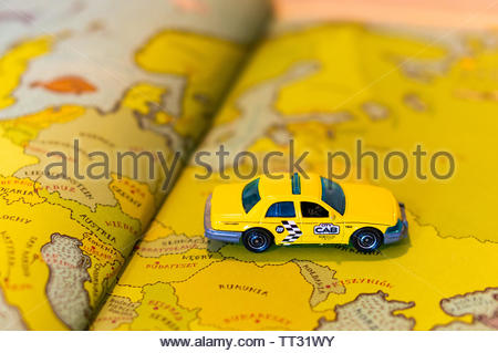 Mattel Matchbox yellow toy Ford Crown Victoria taxi car on a page with European map from a open atlas book on circa June 2019 in Poznan, Poland. - Stock Image