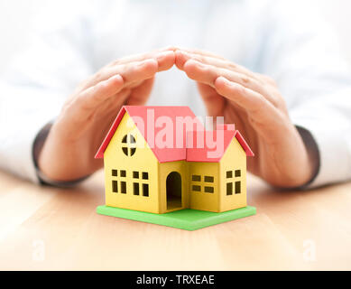 Colorful toy house covered by hands - Stock Image