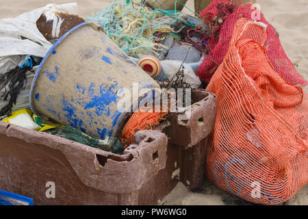 Plastic fishing containers nets and other rubbish washed up on a beach an example of the many pieces of plastic pollution in the sea around the world - Stock Image