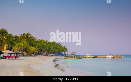 West Bay Roatan Honduras at dawn with few people on the beach. - Stock Image