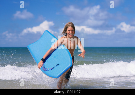 Boy running out of surf with body board - Stock Image
