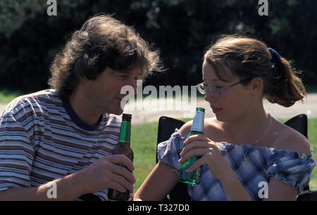 father and teenage daughter drinking bottle of beer - Stock Image