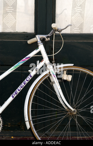 A white Peugeot bike leaning against a black door. - Stock Image