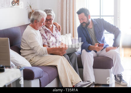 Adult and senior family at home with parents and son - caucasian people sitting on the sofa working with technology devices laptop and phone together  - Stock Image