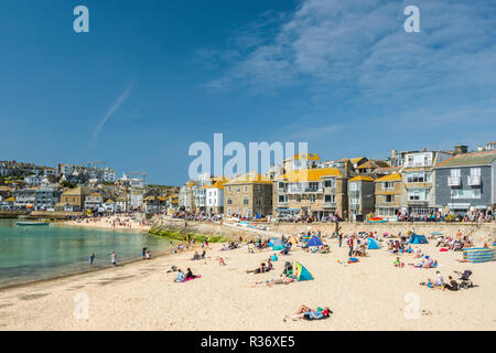 Holidaymakers enjoy sunbathing on Porthmeor beach in St Ives, Cornwall, England on a sunny day - Stock Image