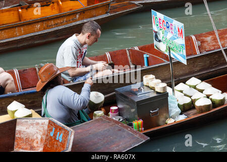 Damnoen Saduak - 4th March 2014: A man buying a coconut from a vendor. The floating market is very famous. - Stock Image
