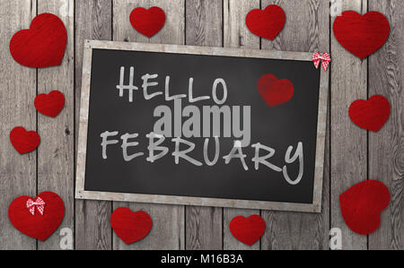 Blackboard with words hello february, surrounded by red hearts, on vintage wooden background - Stock Image